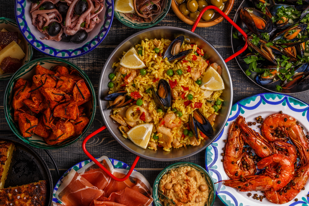 Typical spanish tapas concept. Concept include slices jamon, bowls with olives, anchovies, spicy potatoes, mashed chickpeas, shrimp, calamari, manchego with quince marmalade, pans with tortilla, paella, mussels on a wooden table.